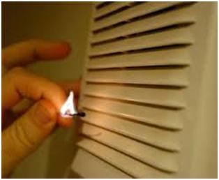 Зажженная спичка возле вентиляционной решетки