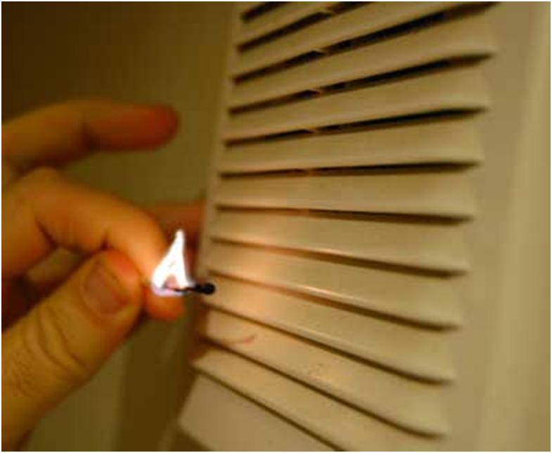 Зажженная спичка рядом с вентиляционной решеткой